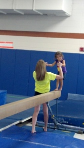 After a couple distractions, Ellie gets a smile while on the balance beam. Gymnastics can be fun!